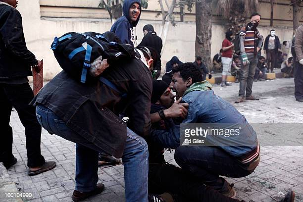 An Egyptian protester tries to carry an injured man away from clashes with Egyptian riot police during a protest following the announcement of the...
