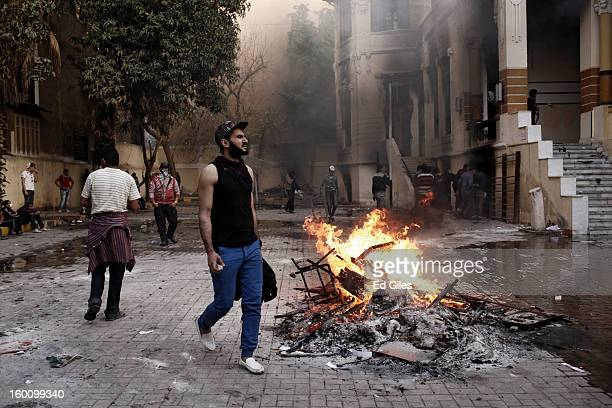An Egyptian protester walks past a fire lit in the grounds of a school during a protest following the announcement of the death penalty for 21...