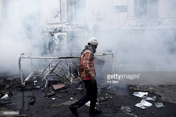 An Egyptian protester walks through a cloud of tear gas fired by Egyptian riot police during a protest following the announcement of the death...