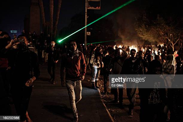 An Egyptian protester walks through a crowd toward nearby riot police during clashes near Tahrir Square on January 27 2013 in Cairo Egypt Violent...