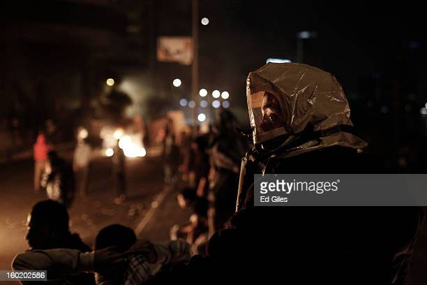 An Egyptian protester wears a makeshift gas mask during clashes with riot police near Tahrir Square on January 27 2013 in Cairo Egypt Violent...