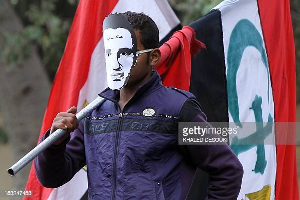 An Egyptian protester wears a mask of Khaled Said a youth who died following police questioning before the revolution in 2010 as he holds up an...