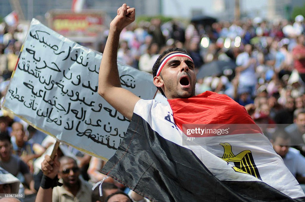 An Egyptian protester wrapped with his n : News Photo