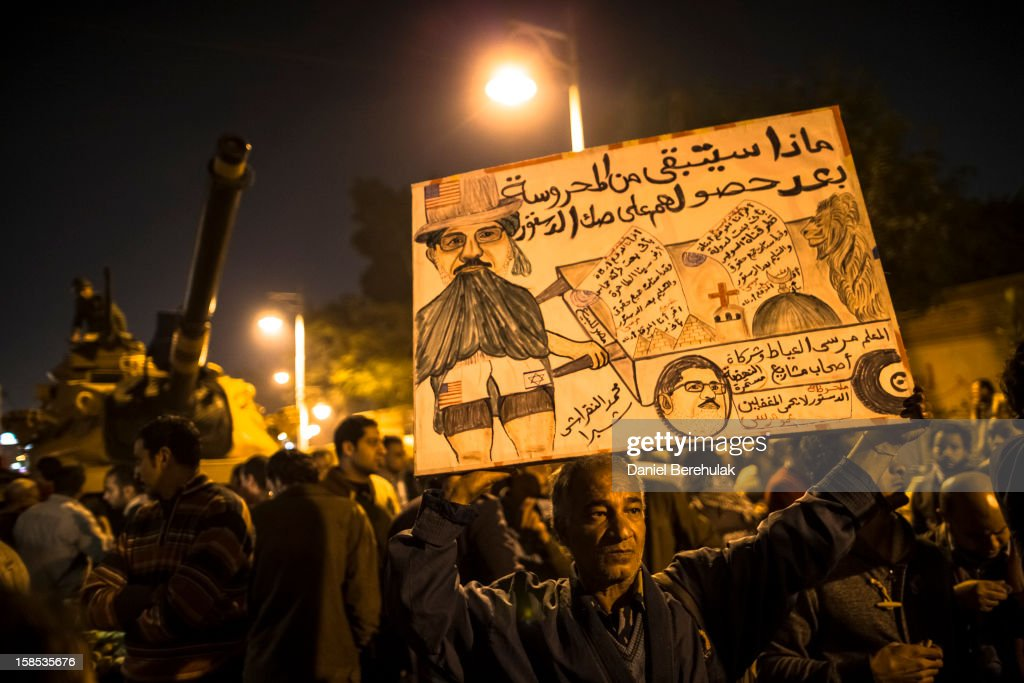An Egyptian protestor opposing president Mohammed Morsi holds up a placard during a demonstration at the Presidential Palace on December 18, 2012 in Cairo, Egypt. Hundreds of people gathered in front of the Presidential Palace and in Tahrir Square to protest against President Mohammed Morsi and the alleged rigging of the first round of voting in the constitutional referendum.
