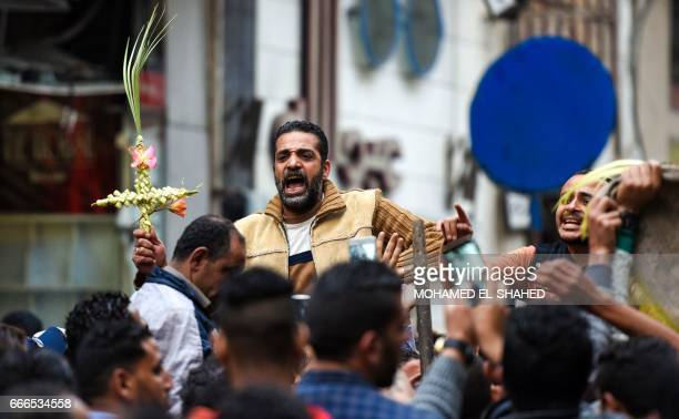 An Egyptian raises a cross made of palm leaves originally intended for Palm Sunday celebrations as he is being lifted by others gathering outside the...