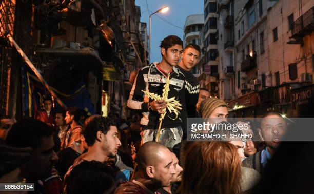 An Egyptian raises a cross made of palm leaves originally intended for Palm Sunday celebrations during a gathering outside the Coptic Orthodox...