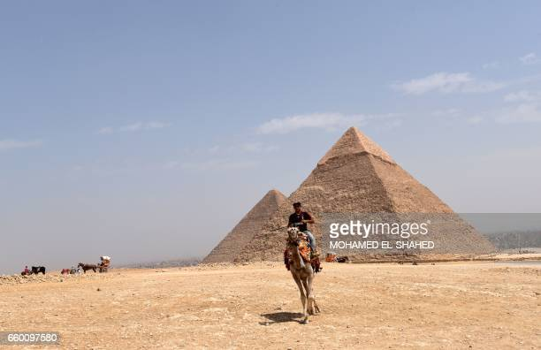 An Egyptian rides a camel past the pyramid of Khafre on March 29 2017 on the Giza Plateau on the southwestern outskirts of the capital Cairo / AFP...