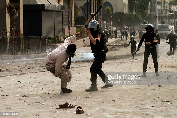 An Egyptian riot policeman hits a protester during clashes near Cairo's Tahrir Square on January 28 2013 Egypt's cabinet approved a draft law that...