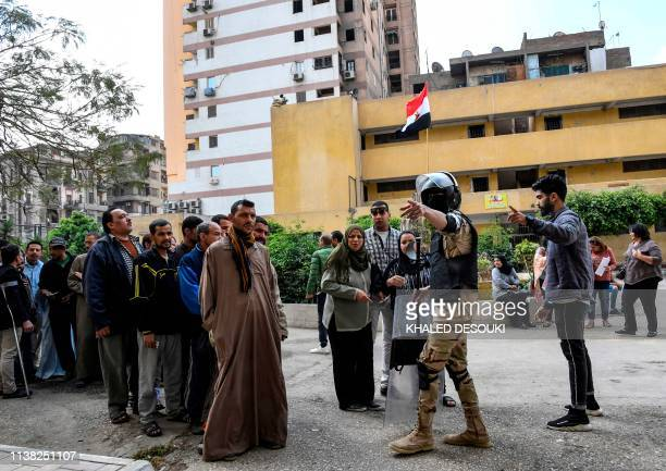 An Egyptian soldier and a youth direct voters to polling stations as they prepare to vote in a referendum on constitutional amendments at a school in...