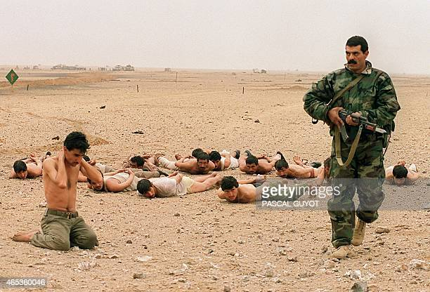 An Egyptian soldier guards Iraqi POWs 25 February 1991 in the Kuwaiti desert on the second day of the allied ground offensive against Iraqi army