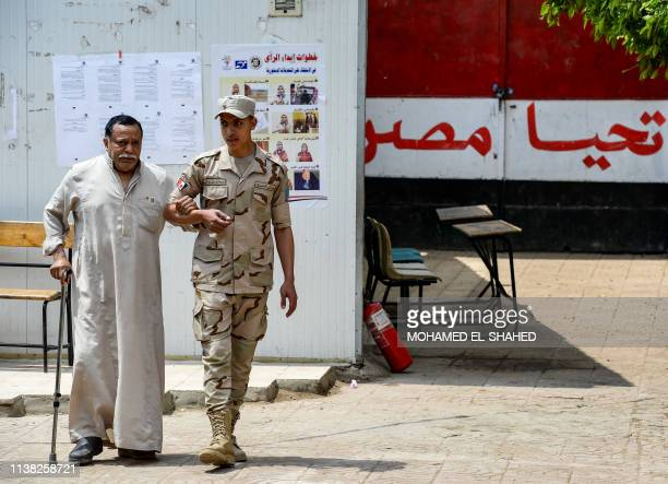 An Egyptian soldier helps an elderly man to a polling station as he arrives to vote in a referendum on constitutional amendments at a school in the...