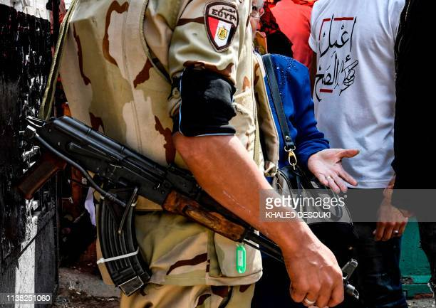 An Egyptian soldier speaks with a woman with a youth behind her wearing a tshirt with text in Arabic reading do the right thing part of a nationwide...