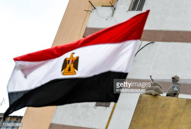 An Egyptian soldier stands on guard near a waving national flag as citizens arrive to cast votes in a referendum on constitutional amendments at a...