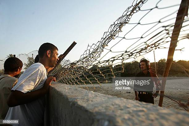 An Egyptian soldier talks to Palestinians through the fence of the now EgyptianPalestinian controlled border September 13 2005 in Rafah southern Gaza...