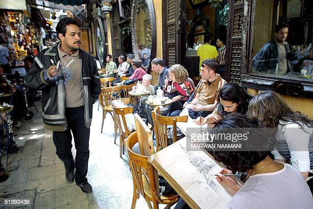 An Egyptian street vendor looks at art students sketching as they sit at the traditional cafe of alFishawi in Cairo's historical Khan alKhalili bazar...
