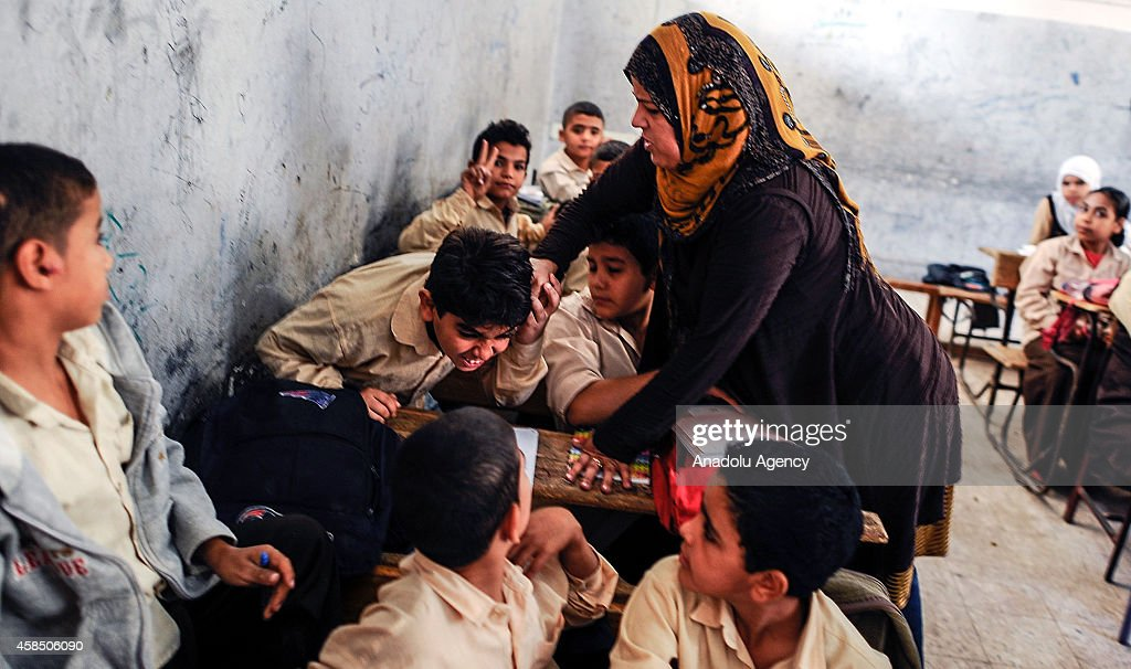 An Egyptian student is punished by his teacher during the lesson at a primary school, where nearly 2 thousand students get education, after the Egyptian national anthem performance in Baragil neighborhood of Giza, Egypt on October 30, 2014. Head master of the school complains about the crowded classroom sizes, reaching up to 70, lack of the desks and other impossibilities. Formal education, at every level, is provided freely at state schools in Egypt. Downswing due to the ongoing 4-year unrest, Egypt tries to overcome many difficulties and uncertainties.