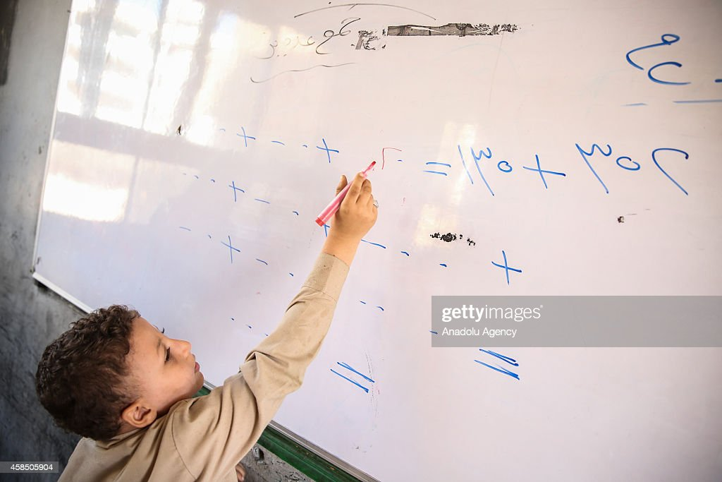 An Egyptian student tries to solve a problem during a lesson at the class of a primary school, where nearly 2 thousand students get education, in Baragil neighborhood of Giza, Egypt on October 30, 2014. Head master of the school complains about the crowded classroom sizes, reaching up to 70, lack of the desks and other impossibilities. Formal education, at every level, is provided freely at state schools in Egypt. Downswing due to the ongoing 4-year unrest, Egypt tries to overcome many difficulties and uncertainties.