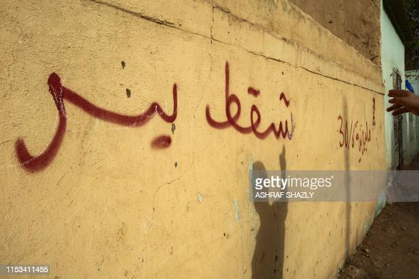 An Egyptian student who fled political repression in Egypt and moved to Sudan gestures as he stands next to graffiti on a wall reading in Arabic...