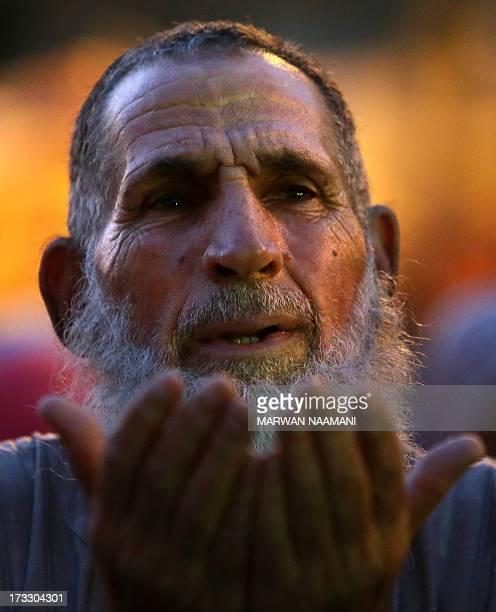 An Egyptian supporter of the Muslim Brotherhood and Egypt's ousted president Mohamed Morsi performs dusk prayer outside Cairo's Rabaa alAdawiya...