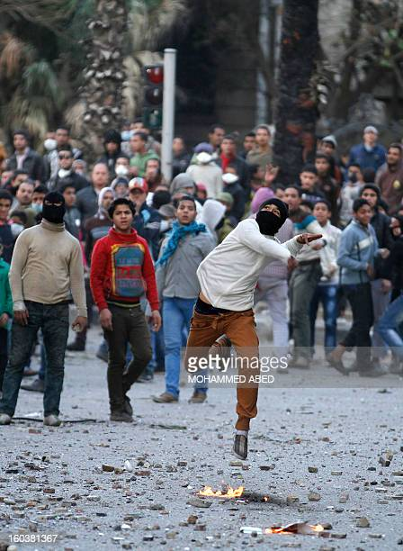 An Egyptian throws a molotov cocktail during clashes with riot police near Cairo's Tahrir Square on January 30 2013 Egyptian opposition leaders...
