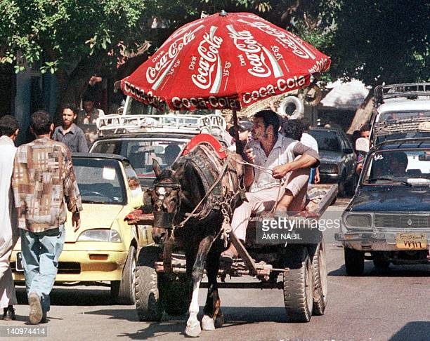 An Egyptian uses a huge Coca Cola umbrella to protect himself from Cairo's scorching sun 12 July 1999 as he leads a donkey cart in one of the crowded...