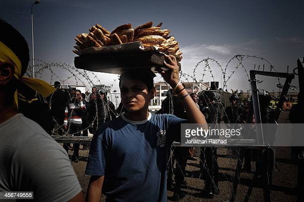 An Egyptian vendor poses for a photo during a protest in solidarity with Egypt's deposed president Mohamed Morsi outside Police Academy in Cairo. 4...