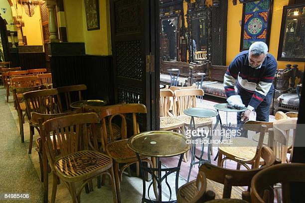An Egyptian waiter cleans a table as he opens the popular ElFishawi coffee shop in the tourist bazaar close to the AlHussein mosque in Cairo early on...