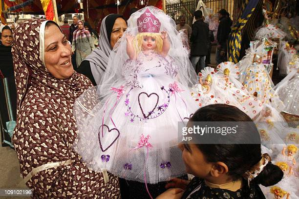 An Egyptian woman and her daughter buy a bride doll during a visit to the Sayida Zeinab neighborhood market in central Cairo on February 15 as...