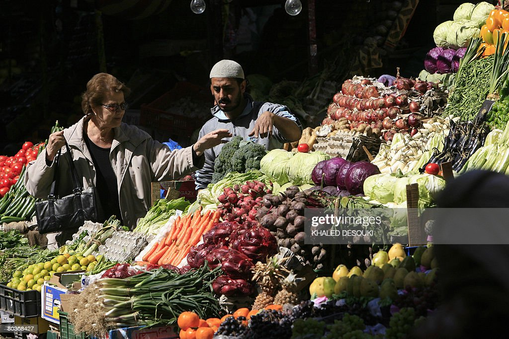 An Egyptian woman buys vegetables at a m : News Photo