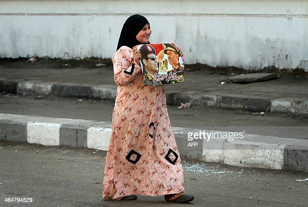 An Egyptian woman carries a poster bearing portraits of late Egyptian president Anwar Sadat alongside Egypt's Defence Minister army chief Abdel...