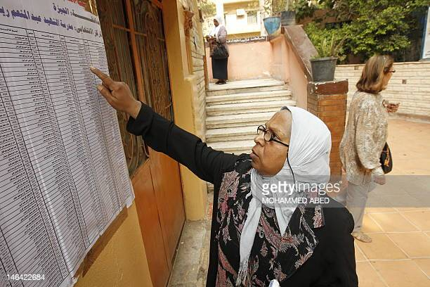 An Egyptian woman checks the lists before voting at a polling station in Cairo on June 16 2012 in a divisive presidential runoff pitting ousted...