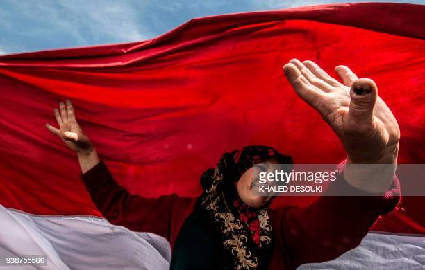 TOPSHOT An Egyptian woman dances before a large national flag in Cairo's northern suburb of Shubra alKhaymah on the second day of voting in the 2018...