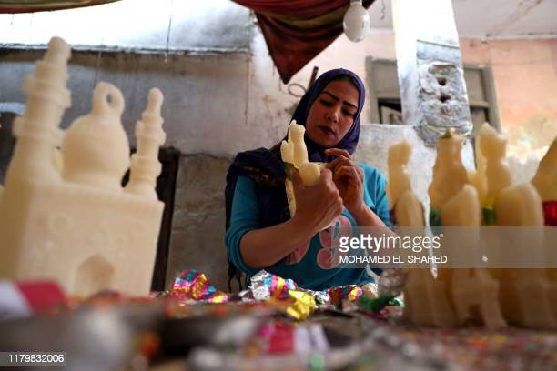An Egyptian woman decorates traditional sugar statuettes in the capital Cairo on November 2 ahead of celebrations of the Muslim Prophet Mohammed's...