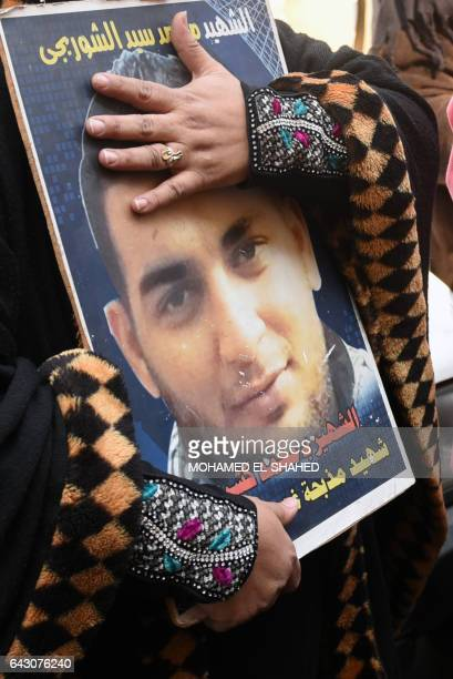 An Egyptian woman holds a portrait of a family member and a victim of the Port Said massacre outside the Court of Cassation following the court's...