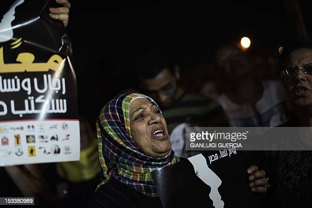 An Egyptian woman holds a slogan which reads in Arabic 'Women day Egypt' during a demonstration in front of the presidential palace in Cairo on...