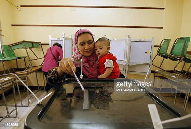 An Egyptian woman holds her child as she casts her ballot at a polling station in Cairo on June 16 in a divisive presidential runoff pitting ousted...