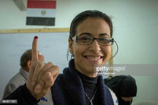 CONTENT] An Egyptian woman holds up her pinky finger to show it has been inked purple to mark that she has voted in the Egyptian constitutional...