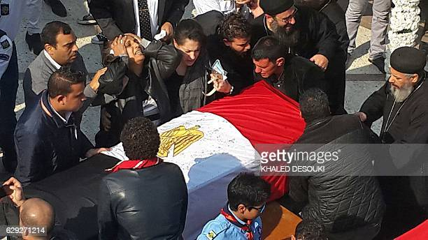 An Egyptian woman reacts next to the coffins of her two daughters during the funeral of the victims of a bomb explosion that targeted a Coptic...