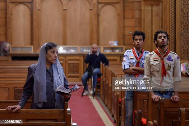 An Egyptian woman recites prayers for victims killed in an attack a day earlier during an early morning ceremony at the Prince Tadros church in...