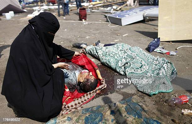 An Egyptian woman shows a dead body lying on the ground after an Egyptian police crackdown on a protest camp by supporters of ousted president...