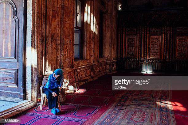 An Egyptian woman sits at the entrance to the Muhammad Ali Mosque in Cairo's Citadel on October 21 2013 in Cairo Egypt The Muhammad Ali Mosque...