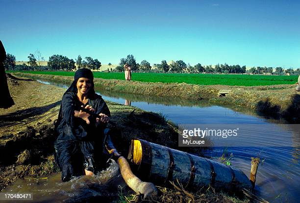 An Egyptian woman turns an Archimedes screw an ancient device used to transfer water from a canal to an adjacent field The Nile Valley canal system...