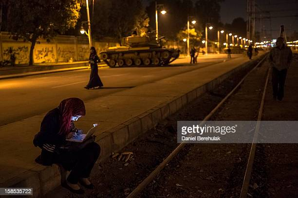 An Egyptian woman types on her laptop prior to the start of a demonstration opposing president Mohammed Morsi at the Presidential Palace on December...