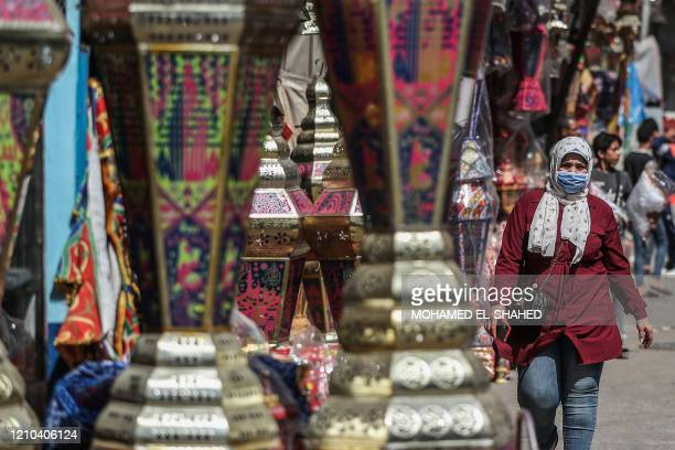 "An Egyptian woman walks by traditional lanterns known in Arabic as ""Fanous"" sold during the Muslim holy month of Ramadan in Cairo's Sayeda Zainab..."
