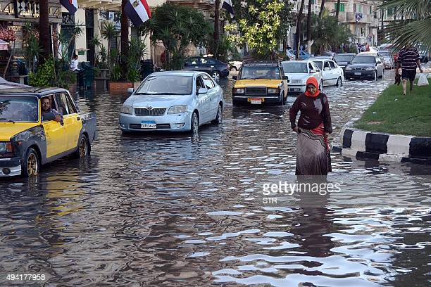 An Egyptian woman walks in a flooded street in Egypt's northern coastal city of Alexandria following heavy rains on October 25 2015 AFP PHOTO / STR