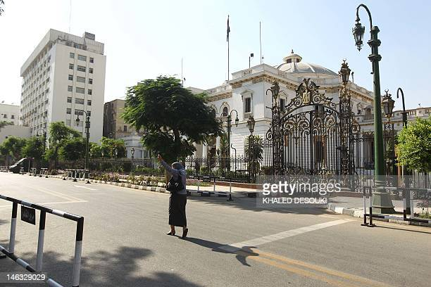An Egyptian woman walks on a deserted street outside the Egyptian parliament building in central Cairo on June 14 2012 Egypt's top constitutional...