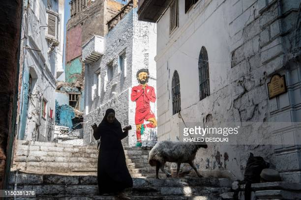 TOPSHOT An Egyptian woman walks past a mural of Egyptian footballer Mohamed Salah in Cairo on June 17 four days ahead of the African Cup of Nations...