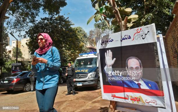 An Egyptian woman walks past an electoral banner commissioned by a member of parliament depicting incumbent President Abdel Fattah alSisi seen with a...