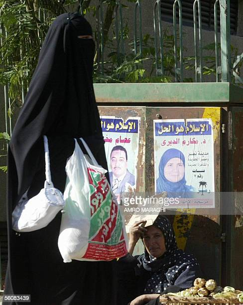 An Egyptian woman walks past campaign posters of Makarem alDeiri in Cairo 04 November 2005 Deiri is standing for election to the Egyptian parliament...