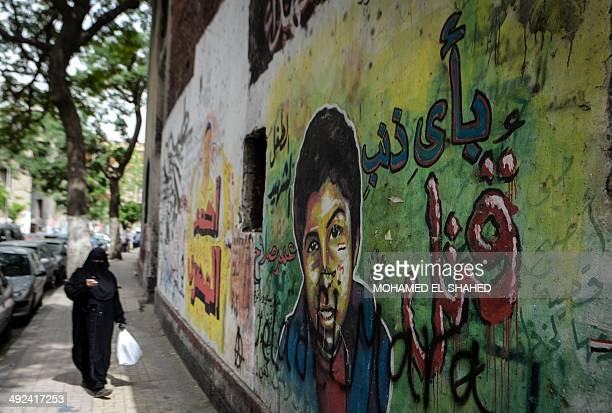 An Egyptian woman walks past graffiti on a wall in Cairo on May 20 2014 AFP PHOTO / MOHAMED ELSHAHED